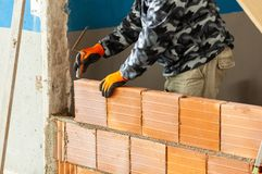 Bricklayer installing brick masonry on interior wall stock images