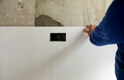 Construction worker putting white porcelain stoneware tiles in the kitchen Stock Photography
