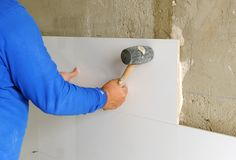 Construction worker putting white porcelain stoneware tiles in the kitchen. Bricklayer laying white tiles with rubber hammer in reforming the kitchen of the Royalty Free Stock Images