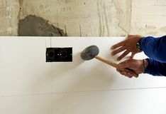 Construction worker putting white porcelain stoneware tiles in the kitchen. Bricklayer laying white tiles with rubber hammer in reforming the kitchen of the Stock Photos