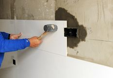 Construction worker putting white porcelain stoneware tiles in the kitchen. Bricklayer laying white tiles with rubber hammer in reforming the kitchen of the Stock Image