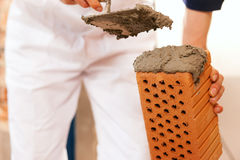 Bricklayer making wall with brick and grout Stock Image