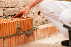 Bricklayer making wall with brick and grout. Bricklayer laying, well, bricks to make a wall, he is pulling grout out of a joint with his trowel. This man is Stock Photos