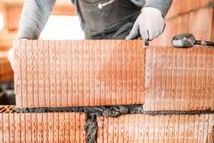 Bricklayer construction worker installing interior brick masonry royalty free stock images