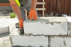 Bricklayer man worker in orange gloves installing block with trowel. Stock Images