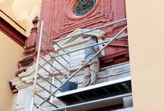 Bricklayer performing the cleaning of the stone facade of a baroque church Stock Photos