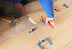 Bricklayer placing a porcelain tile floor in imitation of beechwood Royalty Free Stock Images