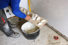 Bricklayer putting cement mortar on tiles Royalty Free Stock Photography