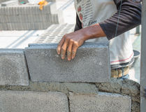 Bricklayer putting down another row of bricks in site Royalty Free Stock Photo