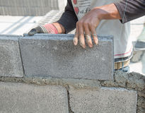 Bricklayer putting down another row of bricks in site Royalty Free Stock Image