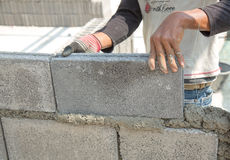 Bricklayer putting down another row of bricks in site Stock Photography