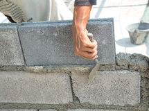 Bricklayer putting down another row of bricks in site Royalty Free Stock Photography