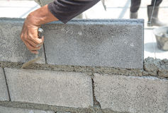 Bricklayer putting down another row of bricks in site Stock Images