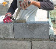 Bricklayer putting down another row of bricks in site Stock Image