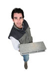 Bricklayer standing with concrete block Royalty Free Stock Image