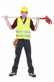Bricklayer standing legs apart. Full-body portrait of bricklayer standing legs apart carrying shovel on his shoulders stock photos