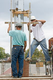 Bricklayer Teamwork. Construction bricklayers measuring and marking for laying brick columns Stock Images