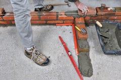 Bricklayer three. Construction of a brick wall by a bricklayer royalty free stock photo