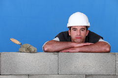 Bricklayer with a trowel. Bricklayer with trowel head resting on arms Stock Image