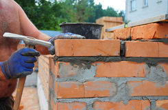 Bricklayer Using a Bricklaying Hammer to Build New Red Brick Wal. L Outdoor. Bricklaying Basics Masonry Techniques Royalty Free Stock Images