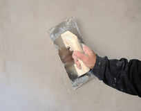 Bricklayer using the trowel to plaster the wall with perlite, very fine plaster for finishes Royalty Free Stock Photos
