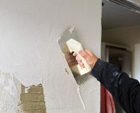 Bricklayer using the trowel to plaster the wall with perlite, very fine plaster for finishes Stock Photo