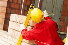 Bricklayer at work with red brick. Bricklaying construction work. bricklayer builder working with red brick Royalty Free Stock Photo