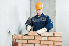 Bricklayer at work with red brick. Construction worker. Portrait of mason bricklayer installing red brick with trowel putty knife outdoors Stock Photo