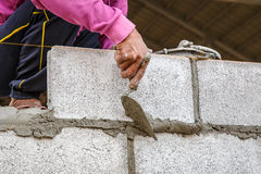Bricklayer worker installing brick masonry on construction site Royalty Free Stock Images
