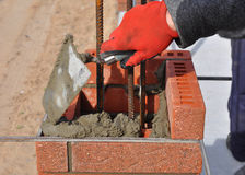 Bricklayer worker installing red blocks and caulking brick masonry. Joints exterior wall with trowel putty knife outdoor Royalty Free Stock Photography