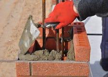 Bricklayer worker installing red blocks and caulking brick masonry Royalty Free Stock Photography
