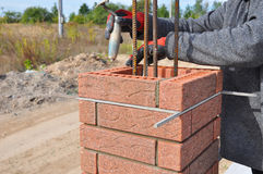 Bricklayer Worker Installing Red Clinker Blocks around Iron Bar. And Caulking Brick Masonry Joints Exterior Wall with Trowel Putty Knife and Fixing with Spirit Stock Image