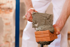 Bricklayer working on construction site Stock Images