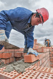 Bricklayer works on 15th floor of building Stock Photos