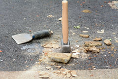 Bricklayers bolster chisel and lump hammer. On floor Royalty Free Stock Photography