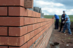 Bricklayers building a house wall. Newly built red brick wall of a newly built house with bricklayers in the background Royalty Free Stock Image