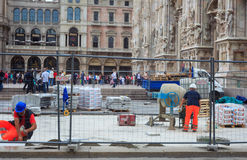 Bricklayers in the construction site. MILAN, ITALY - MAY 26: Bricklayers in the construction site next to the Milan cathedral on May 26, 2014 Royalty Free Stock Images