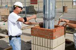 Bricklayers Leveling Bricks. Construction bricklayers leveling bricks as they lay rows to form a column Stock Image