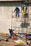 Bricklayers on scaffolding. Bricklayers in safety helmets on scaffolding Royalty Free Stock Photo