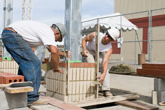 Bricklayers Using Levels. Construction bricklayers leveling brickwork as they construct a column Stock Photography