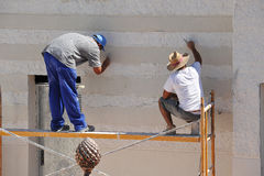 Bricklayers working on the scaffold. Masons during the reform of the facade of a house Royalty Free Stock Photography