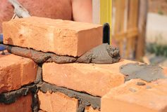 Bricklayer worker installing red blocks and caulking brick masonry joints exterior brick house wall with trowel putty knife Stock Photos