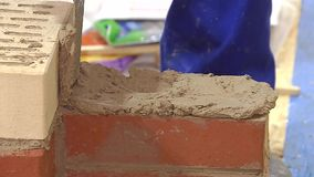 Bricklaying. Close up. White brick is put on the red and leveled stock video footage