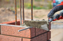 Bricklaying closeup. Bricklayer hand holding a putty knife and building a brick fence column. Building brick Stock Photo