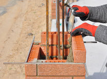 Bricklaying Closeup. Bricklayer hand holding a Putty Knife and Building a Brick Wall Column. With Iron Bar Outdoor Stock Image