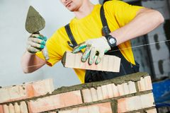 Bricklayer builder worker laying bricks wall. Bricklaying construction work or walling. bricklayer builder working laying bricks Stock Image
