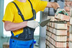 Bricklayer builder worker laying bricks wall. Bricklaying construction work or walling. bricklayer builder working laying bricks Royalty Free Stock Photography