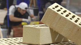 Bricklaying. In the foreground are two brick. In the background a man is putting the bricks stock video footage