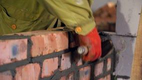 bricklaying Hände, die einen Ziegelstein auf eine Baustelle setzten stock video