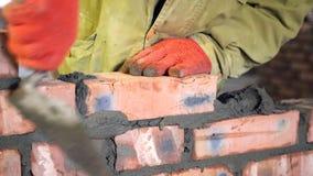 bricklaying Hände, die einen Ziegelstein auf eine Baustelle setzten stock footage